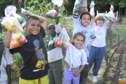 Children holding bags of vegetables.