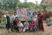 Youth in front of the Kids' Garden sign.