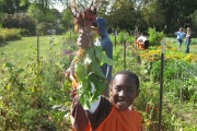 A youth holding some vegetables.