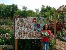 A girl in front of the Kids' Garden sign.