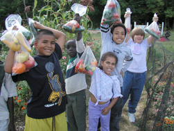 A group of kids holding bags of vegetables.
